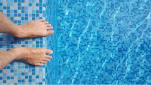 Muž stojí na okraji bazénu a doufá, že nechytne bradavice